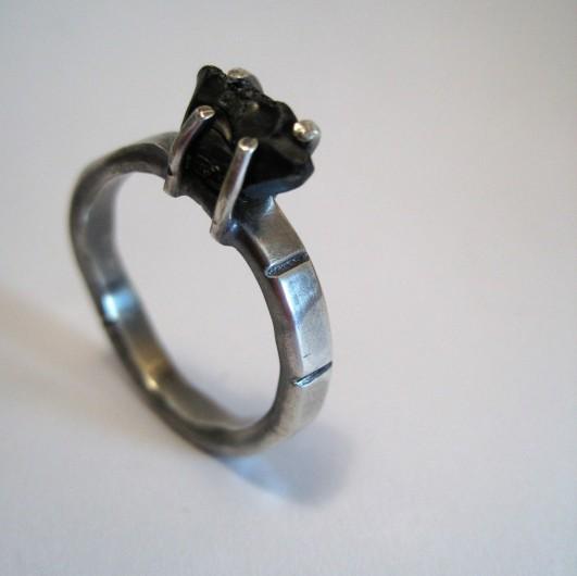 Rujo-sormus, kivenä raaka hiomaton musta onyksi.